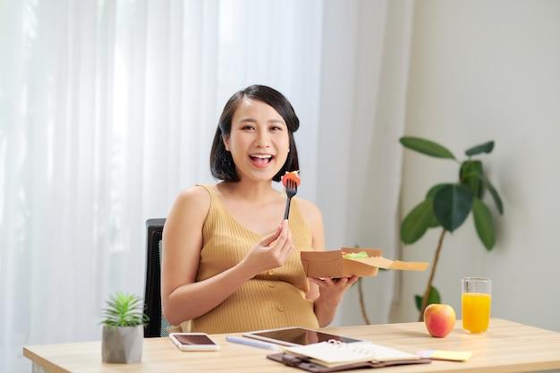 Una giovane donna incinta in piedi in ufficio a casa e utilizza un tablet pc
