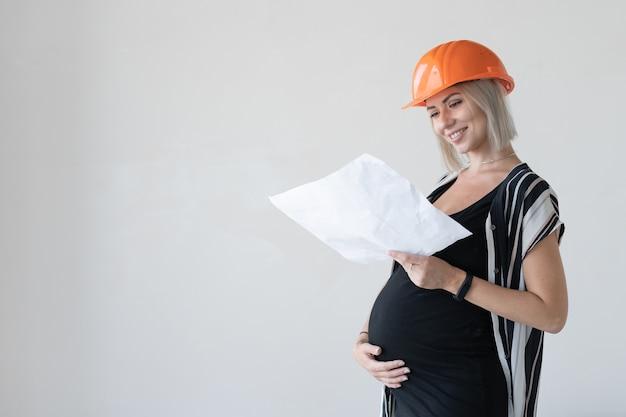 Giovane donna incinta che indossa un casco protettivo da costruzione sulla testa. guarda un foglio con disegni. nuova casa di famiglia. posto per il testo. si erge contro un muro bianco.