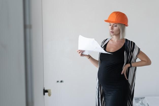 Giovane donna incinta che indossa un casco protettivo da costruzione sulla testa. guarda il foglio delle attività. si erge contro un muro bianco.