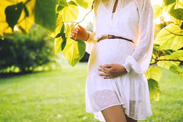 La giovane donna incinta in vestito bianco tiene le mani sulla sua pancia sul fondo verde della natura
