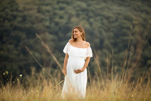 Giovane donna incinta in abito bianco presso il campo estivo