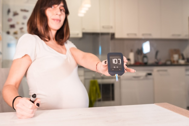 Giovane donna incinta con un autotest del diabete gestazionale per controllare lo zucchero, con un risultato positivo