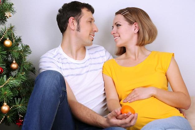 Giovane donna incinta con suo marito seduto sul pavimento vicino all'albero di natale a casa