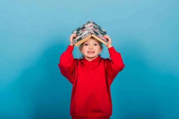 Il giovane bambino prescolare impara leggendo un libro, isolato sull'azzurro