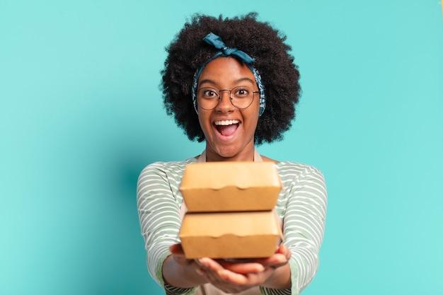 Giovane donna abbastanza afro consegna con scatole di hamburger da asporto