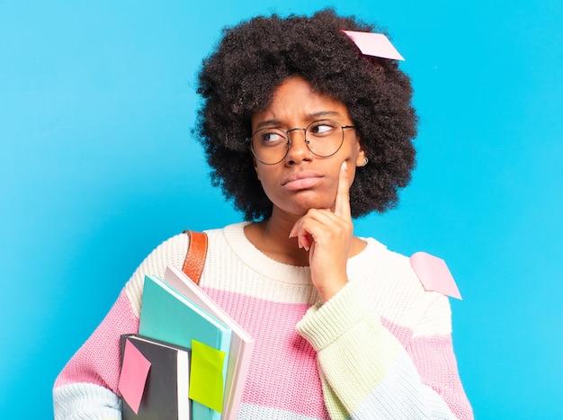 Giovane bella studentessa afro con libri e quaderni