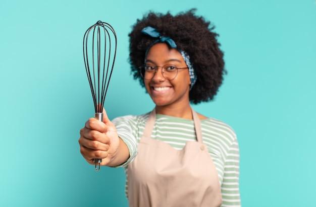 Giovane chef donna abbastanza afro con un mixer