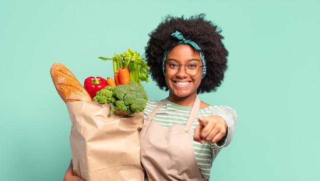 Giovane bella donna afro che ride ad alta voce a uno scherzo esilarante, si sente felice e allegra, si diverte e tiene in mano un sacchetto di verdure