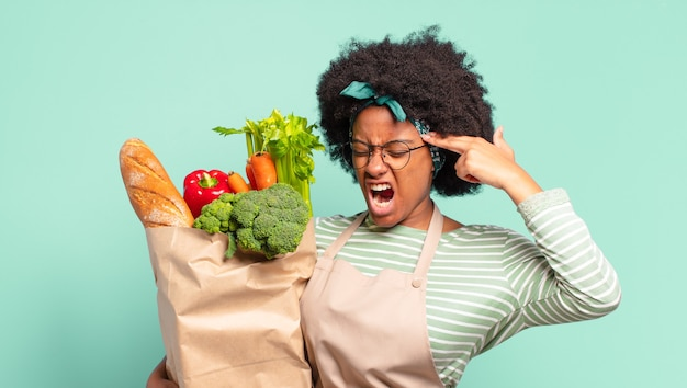 Giovane bella donna afro che sembra infelice e stressata, gesto di suicidio che fa segno di pistola con la mano, indicando la testa e tenendo un sacchetto di verdure