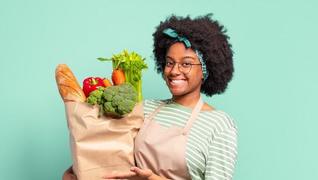 Giovane bella donna afro che sorride allegramente, indicando il lato e verso l'alto tenendo un sacchetto di verdure