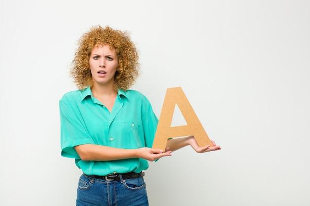 Giovane bella donna afro sorpresa, scioccata, stupita, con in mano la lettera a dell'alfabeto per formare una parola o una frase.