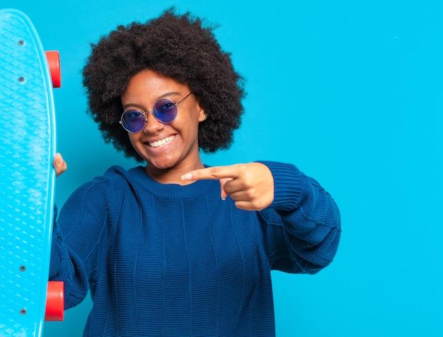 Giovane bella donna afro con uno skateboard