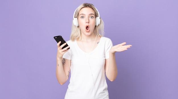 Giovane bella donna albina stupita, scioccata e stupita da un'incredibile sorpresa con cuffie e smartphone