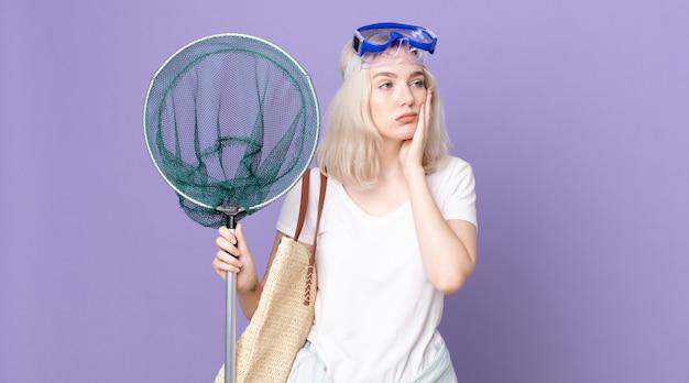 Giovane bella donna albina che si sente annoiata, frustrata e assonnata dopo una noiosa con gli occhiali e una rete da pesca