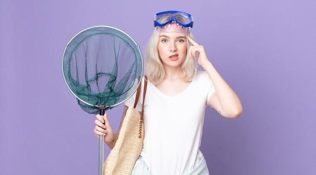 Giovane bella donna albina che si sente confusa e perplessa, mostrando che sei pazzo con gli occhiali e una rete da pesca