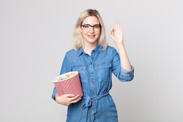 Giovane bella donna albina che si sente felice, mostra approvazione con un gesto ok con un secchio di pop corn
