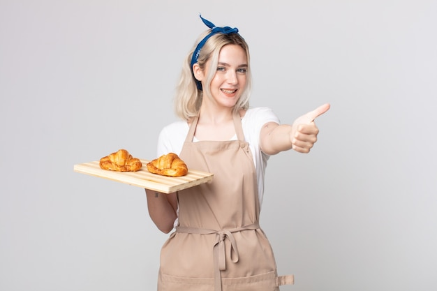 Giovane bella donna albina che si sente orgogliosa, sorride positivamente con il pollice in alto con un vassoio di croissant