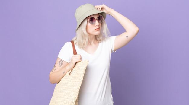 Giovane bella donna albina che si sente perplessa e confusa, grattandosi la testa. concetto di estate