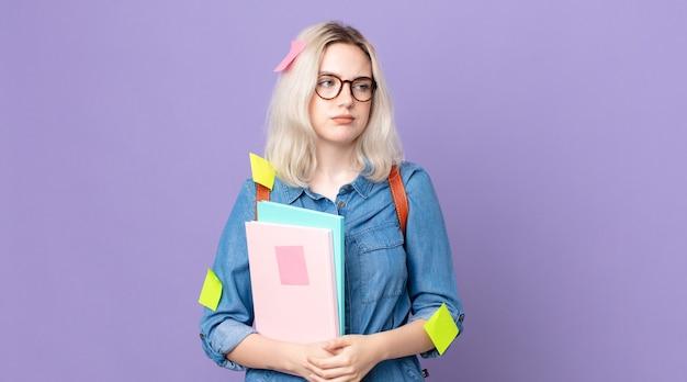 Giovane bella donna albina che si sente triste, sconvolta o arrabbiata e guarda di lato. concetto di studente