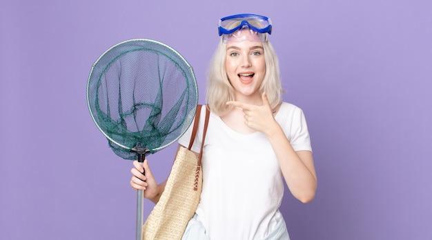 Giovane bella donna albina che sembra eccitata e sorpresa che indica il lato con gli occhiali e una rete da pesca