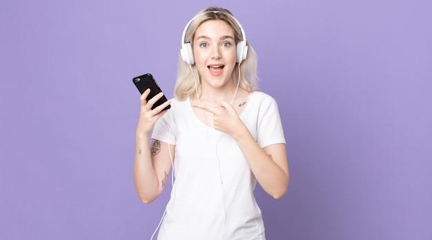 Giovane bella donna albina che sembra eccitata e sorpresa indicando il lato con cuffie e smartphone