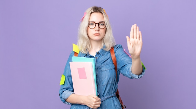 Giovane bella donna albina che sembra seria mostrando il palmo aperto che fa il gesto di arresto. concetto di studente