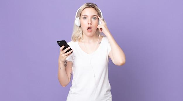 Giovane bella donna albina che sembra sorpresa, realizzando un nuovo pensiero, idea o concetto con cuffie e smartphone