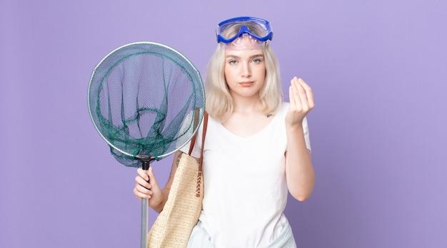Giovane bella donna albina che fa un gesto di denaro o di denaro, dicendoti di pagare con gli occhiali e una rete da pesca
