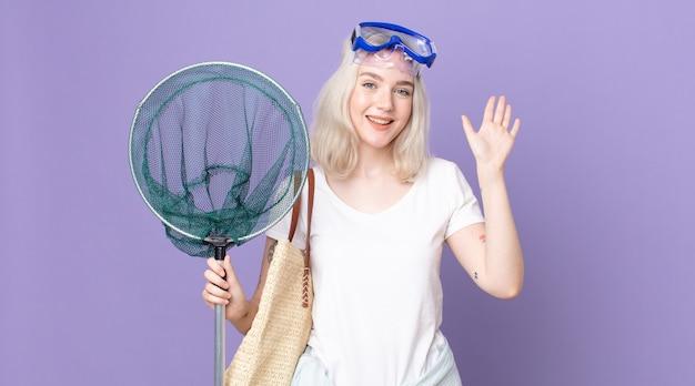 Giovane bella donna albina che sorride felicemente, agitando la mano, accogliendoti e salutandoti con gli occhiali e una rete da pesca