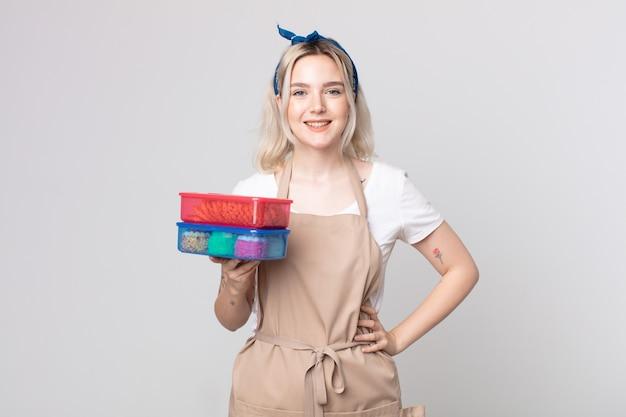 Giovane bella donna albina che sorride felicemente con una mano sull'anca e fiduciosa in possesso di cibo tupperwares