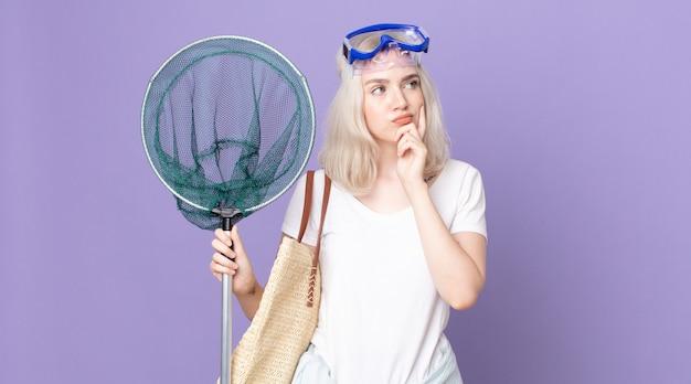 Giovane bella donna albina che pensa, si sente dubbiosa e confusa con gli occhiali e una rete da pesca