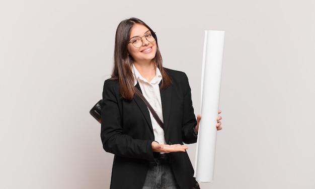 Giovane bella donna architetto che sorride allegramente, si sente felice e mostra un concetto nello spazio della copia con il palmo della mano