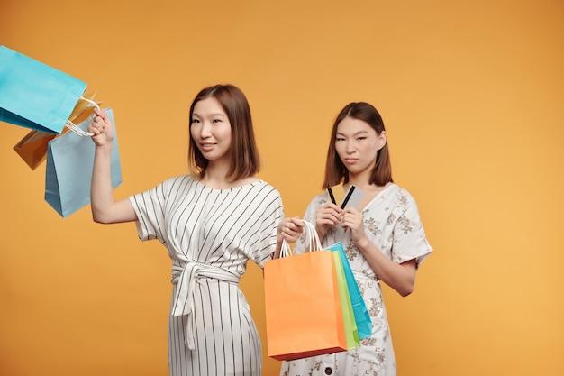 Giovani belle consumatrici asiatiche con sacchetti di carta che si godono lo shopping mentre la sorella gemella infastidita con carte di credito in piedi dietro
