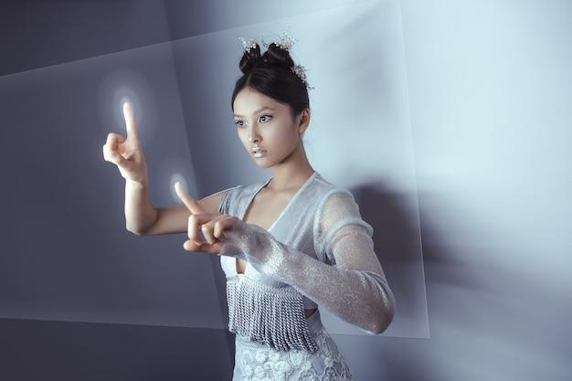 Giovane femmina abbastanza asiatica che tocca lo schermo digitale dell'ologramma