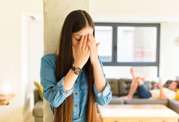 Giovane donna abbastanza asiatica che copre gli occhi con le mani con uno sguardo triste e frustrato di disperazione, pianto, vista laterale
