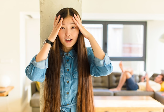 Giovane donna abbastanza asiatica che si sente inorridita e scioccata, alzando le mani alla testa e in preda al panico per un errore
