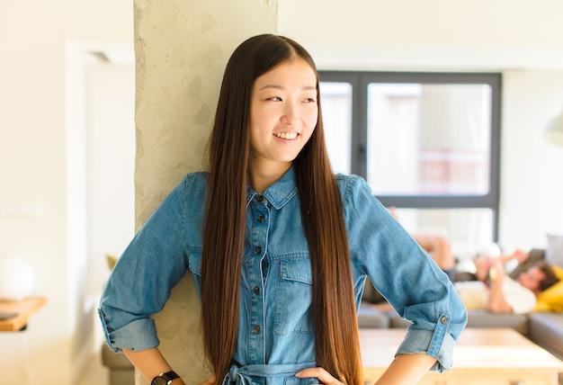 Giovane donna abbastanza asiatica che sembra felice, allegra e sicura di sé, sorridendo con orgoglio e guardando a lato con entrambe le mani sui fianchi