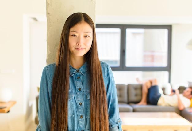 Giovane donna abbastanza asiatica che sembra orgogliosa, sicura di sé, fredda, sfacciata e arrogante, sorridente, sentendosi di successo