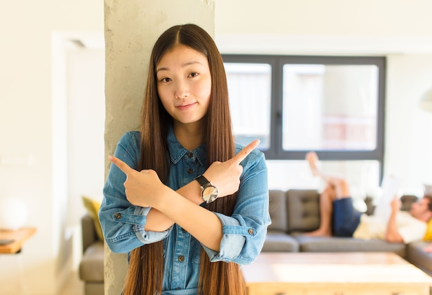 Giovane donna abbastanza asiatica che sembra perplessa e confusa, insicura e che punta in direzioni opposte con dubbi
