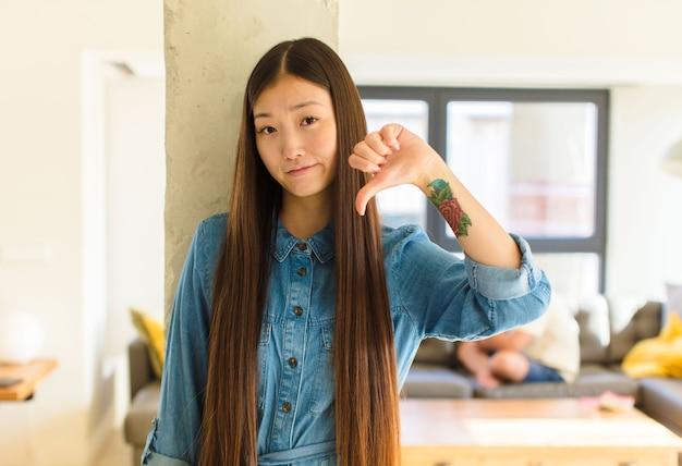 Giovane donna abbastanza asiatica che sembra triste, delusa o arrabbiata, mostrando i pollici verso il basso in disaccordo, sentendosi frustrata