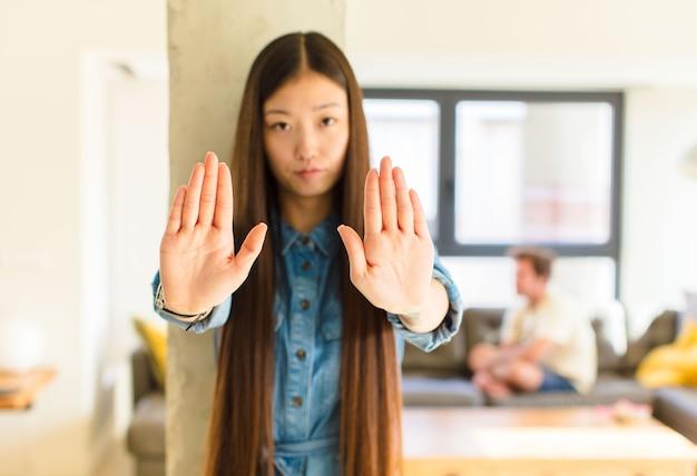 Giovane donna abbastanza asiatica che sembra seria, infelice, arrabbiata e scontenta di vietare l'ingresso o dire basta con entrambi i palmi aperti