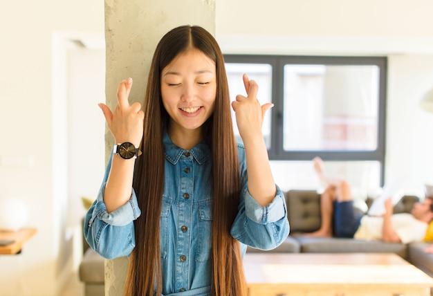 Giovane donna abbastanza asiatica che sorride e incrocio ansiosamente entrambe le dita, sentendosi preoccupata e desiderando o sperando buona fortuna