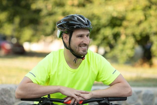 Giovane uomo abbastanza atletico in piedi con la bicicletta nel parco estivo