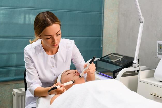La giovane e graziosa estetista esegue una procedura di miostimolazione microcorrente facciale