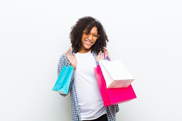 Giovane donna di colore graziosa con i sacchetti della spesa contro la parete bianca