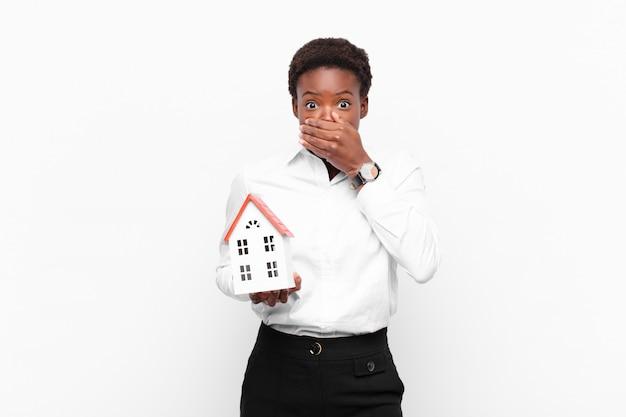 Giovane donna piuttosto nera che copre la bocca con le mani con un'espressione scioccata e sorpresa, mantenendo un segreto o dicendo oops con un modello di casa