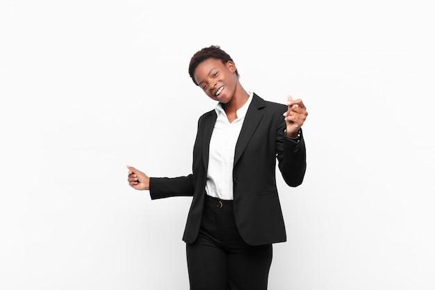 Giovane donna piuttosto nera che sorride, sentirsi spensierata, rilassata e felice, ballare e ascoltare musica, divertirsi a una festa contro il muro bianco