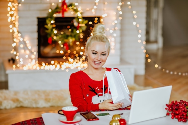 Giovane donna abbastanza bionda in maglione rosso di inverno che tiene il pacchetto regalo bianco.