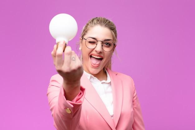 Giovane donna bionda graziosa che ha un'idea con una lampadina