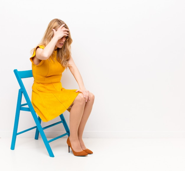Giovane bella donna bionda che sembra stressata, stanca e frustrata, asciuga il sudore dalla fronte, si sente senza speranza ed esausta contro la parete di colore piatto